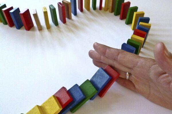 Eine Hand unterbricht umfallende Dominosteine